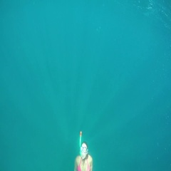 SLOW MOTION UNDERWATER: Girl snorkeling in sea, swimming to the surface for air Stock Footage