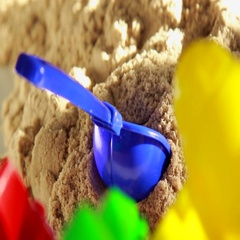 Colorful beach toys lying in kinetic sand under sun rays, close up Stock Footage