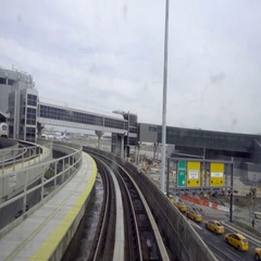 Air Train at JFK Airport riding on track with taxi cabs below Stock Footage