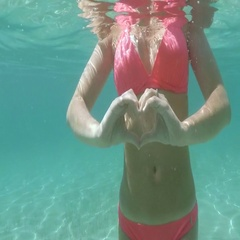 UNDERWATER: Unrecognizable girl standing in sea showing heart sign with fingers Stock Footage