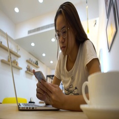 4K Asian woman using Smart Phone and laptop for read something in coffeeshop-Dan Stock Footage