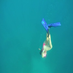 SLOW MOTION UNDERWATER: Pretty woman in bikini snorkeling in crystal clear ocean Stock Footage