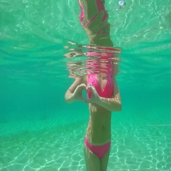 UNDERWATER: Fit woman standing in ocean making heart shaped symbol with fingers Stock Footage
