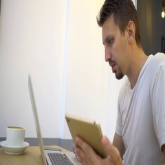 4K Caucasian man is busy to using laptop and tablet for work in coffeeshop-Dan Stock Footage
