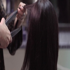 Hairstylist straightening the long black hair of a female client using a heated Stock Footage