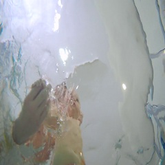 Underwater: the man bathing his little kid in the child pool Stock Footage