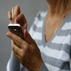 Elderly Woman Browsing Online on Smartphone, White Background Stock Footage