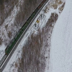 Aerial view of cargo train delivering goods, fuel, petrolium in winter Stock Footage