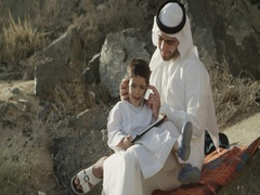 Arab man with son talking on mobile. Stock Footage