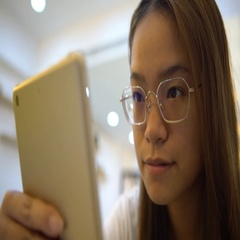 4K Asian woman is smiling when using tablet touch screen in a coffeeshop-Dan Stock Footage