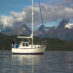 Attractive Sailboat Sitting in Calm Waters Mountain Backdrop Stock Footage