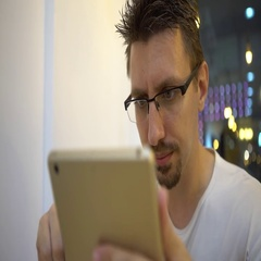 4K Caucasian Man in a coffeeshop using tablet while drinking coffee-Dan Stock Footage