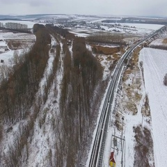 Cargo train delivering goods, fuel, petrolium in winter. Aerial. 4K Stock Footage