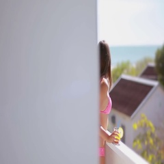 Girl enjoying the sea view while standing on the balcony of the resort Stock Footage