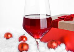 Glass of red wine on snow with christmas balls on white background Stock Photos
