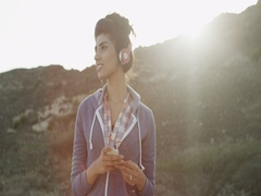 Expat woman holding mobile and listening music on headphones. Stock Footage