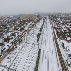 Long freight train coming on the railroad station in winter. Aerila shoot Stock Footage