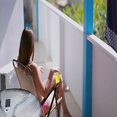 Elegant female basking in the sun while sitting in a chair blue-white terraces Stock Footage