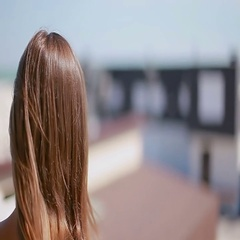 Brown hair fluttering in the wind against the backdrop of of beach houses Stock Footage