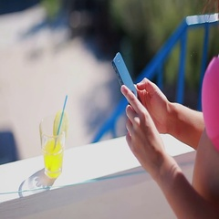 Girl in a pink a swimsuit photographing lemon cocktail on a smartphone Stock Footage