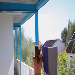 Graceful girl in a swimming suit attaches clothespins to the towels Stock Footage