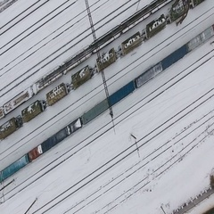 Long freight train coming on the railroad station in winter. Aerial shoot Stock Footage