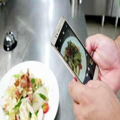 Caesar salad on mobile phone screen, chef photographs food on professional Stock Footage