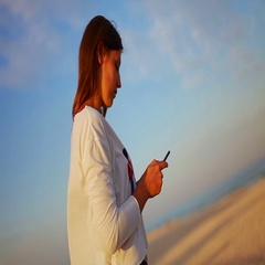 Beautiful girl uses a mobile phone on the beach Arkistovideo