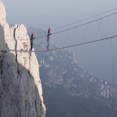 Two Girl Walking Along a Rope Bridge Over The Precipice at High Altitude Stock Footage