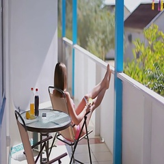 Girl in a pink swimsuit finishes her drink and goes out from the balcony Stock Footage