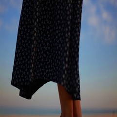 Black and white patterned female skirt fluttering in the wind on the sea shore Stock Footage