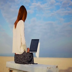 Lady talking on the phone with a laptop on his knees, sitting on a sandy beach Stock Footage