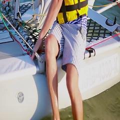 Man and woman jump on board a sailing catamaran Stock Footage