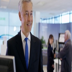 4K Bank worker at service desk assists customer with an account query Stock Footage