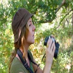 Female birdwatcher brings binoculars up to look at something. Stock Footage