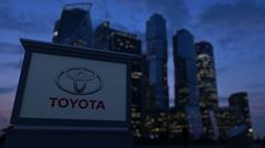 Street signage board with Toyota logo in the evening. Blurred business district Stock Illustration