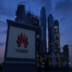 Street signage board with Huawei logo in the evening. Blurred business district Stock Footage