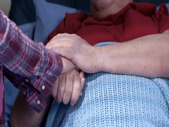 Mature hospital patient holds hands with visiting daughter 4K Stock Footage