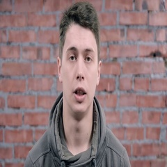 Young man in grey hoody speak on camera. Brick wall background. Audition Stock Footage
