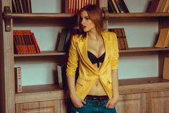 Sexy girl in a yellow jacket unbuttoned looking away Stock Photos