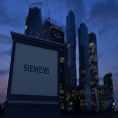 Street signage board with Siemens logo in the evening. Blurred business district Stock Footage