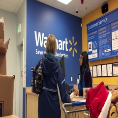 Woman returning goods at customer service counter inside Walmart store Stock Footage