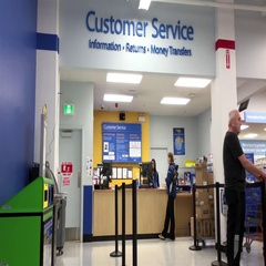 People returning goods at customer service counter inside Walmart store Stock Footage