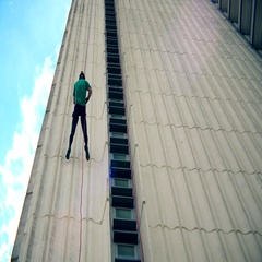 Fearless man descend down with cord on skyscraper wall. Blue cloudy sky Stock Footage