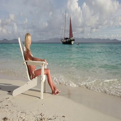 Young woman relaxing in a beach chair on white bay, jost van dyke Stock Footage