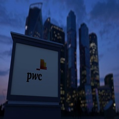 Street signage board with PricewaterhouseCoopers PwC logo in the evening Stock Footage