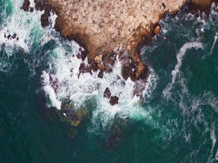 Aerial view of rocky coastline with crop fields Stock Footage