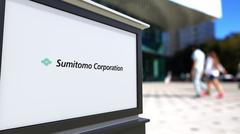 Street signage board with Sumitomo Corporation logo. Blurred office center and Stock Illustration