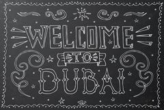 Welcome to Dubai. Hand drawn vintage hand lettering on black chalkboard.  Piirros