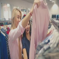 Blonde and brunette looking for clothes with clothes on Stock Footage